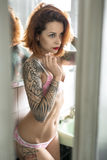 Tattooed girl in bathroom. Redhead girl with colorful tattoos stands in the bathroom with white tiled walls. She wears a rose lingerie. Beauty looks forward and royalty free stock photography