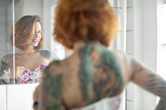 Tattooed girl in bathroom. Smiling girl with colorful tattoos looks into the mirror in the bathroom with white tiled walls. She wears a bright lingerie with stock photo
