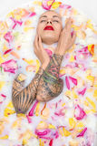 Tattooed girl posing in bath. Charming girl with closed eyes and parted lips lies in the bath full of water with milk and colorful flower petals. She has stock images