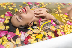 Tattooed girl posing in bath. Wet smiling girl with closed eyes and colorful tattoos lies in the white bath full of water with flower petals. She wears a yellow stock photo