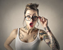 Tattooed girl. A surprised tattooed girl wearing glasses Stock Photography