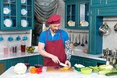 Tattooed man in apron and cap cutting yellow paprika by knife. Cook cooking vegetable salad with red cabbage and paprika. Tattooed guy at kitchen cutting yellow Stock Photography