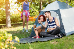 Tattooed guy and lassie sits and drinks beer in front of tent Royalty Free Stock Photo
