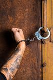 Tattooed hand of a criminal handcuffed Stock Photography