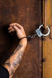 Tattooed hand of a criminal handcuffed Royalty Free Stock Photos