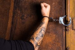 Tattooed hand of a criminal handcuffed Royalty Free Stock Photography
