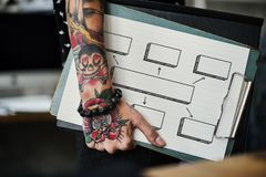 Tattooed hand holding a clipboard royalty free stock photography