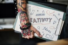 Tattooed hand holding a creativity clipboard stock photography