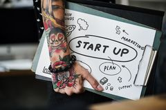 Tattooed hand holding a startup clipboard stock photos