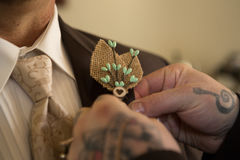Tattooed hands pin burlap corsage on groom Royalty Free Stock Photography