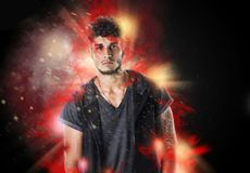 Tattooed hipster young man in burning explosion effect. Confident bearded hipster man in casual outfit looking at camera in burning flame effect stock photo