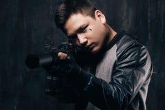 Tattooed killer shoots a sniper rifle close-up stock image