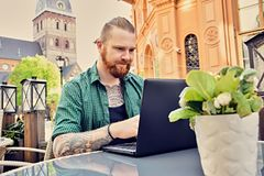 Tattooed male using laptop in an open street cafe. Bearded tattooed male using laptop in an open street cafe in old town Royalty Free Stock Photography