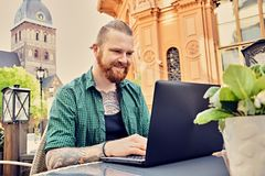 Tattooed male using laptop in an open street cafe. Bearded tattooed male using laptop in an open street cafe in old town Stock Image