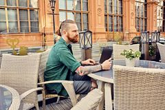 Tattooed male using laptop in an open street cafe. Bearded tattooed male using laptop in an open street cafe in old town Stock Photography