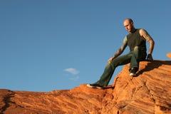 Tattooed man. Sitting on red rocks Royalty Free Stock Photo