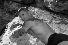 Tattooed man. Man with tattoos laying on his front on a rock,. Taken in black and white stock photo