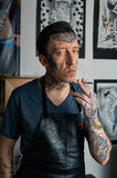 Tattooed man in apron smoking a cigarette Royalty Free Stock Photography