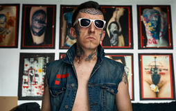 Tattooed man in denim vest and sunglasses in studio Royalty Free Stock Photos