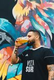 Tattooed Man Drinking on Clear Drinking Glass in Front of Multicolored Painted Wall stock photography