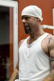 Tattooed man exercising. Half body portrait of tattooed man in white bandanna exercising in gym Stock Image