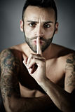 Tattooed man with finger on mouth Stock Photography