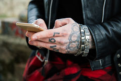 Tattooed man hands with smartphone Stock Photography