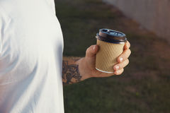 Tattooed man holding a paper coffee cup royalty free stock images