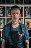 Tattooed man in leather apron Stock Photo