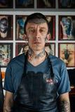 Tattooed man in leather apron Stock Photo