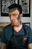 Tattooed man in leather apron making faces Stock Image