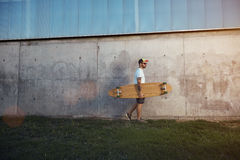 Tattooed man with longboard next to a concrete wall Royalty Free Stock Photo