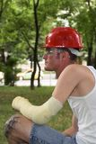 Tattooed man in plaster. Tattooed man with red helmet and hand in plaster Royalty Free Stock Image