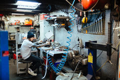 Tattooed Man Repairing Parts in Workshop Stock Photography