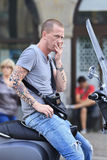 Tattooed man on a scooter. Amsterdam, Holland Royalty Free Stock Image