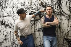 Tattooed men. Two Caucasian tattooed men standing against paint splattered background Royalty Free Stock Photos