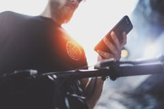 Tattooed muscular male holding mobile phone in hands and using map app for preparing ride road route. Discover urban stock photos