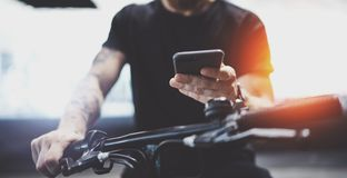Tattooed muscular male holding mobile phone in hands and using map app for preparing ride road route. Discover urban stock image