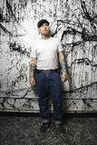 Tattooed and pierced man. Tattooed and pierced man standing against paint splattered background Royalty Free Stock Photo