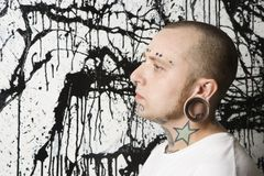 Tattooed and pierced man. Tattooed and pierced man against paint splattered background Royalty Free Stock Photos