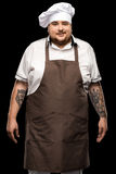 Tattooed smiling young chef standing in white hat and apron stock images
