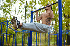 Tattooed Sporty Man Hanging on Bar Royalty Free Stock Images