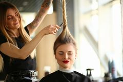 Tattooed Stylist Cutting Hair of Closed Eyes Woman royalty free stock photo