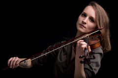 Tattooed violinist woman playing in black background Stock Photos