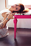 Tattooed Woman. Young tattooed woman with green wooden chair Royalty Free Stock Photo