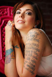 Tattooed Woman. Young tattooed woman with green wooden chair Stock Photography