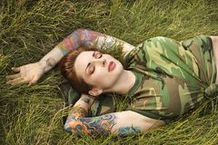 Tattooed woman in camouflage. Stock Photo
