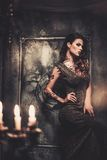 Tattooed woman in old interior. Tattooed beautiful woman in old spooky interior Royalty Free Stock Photography