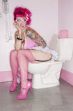 Tattooed woman sitting on toilet seat with her panties down. Tattooed women sitting on toilet seat with her panties down Royalty Free Stock Photos