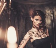 Tattooed woman in spooky interior. Tattooed beautiful woman in old spooky interior royalty free stock images